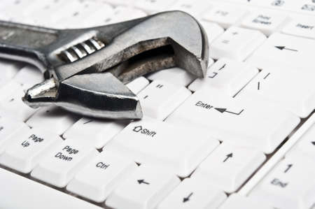 hand tool: Hand tool on an white keyboard Stock Photo