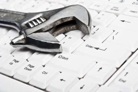 industrial mechanics: Herramienta de mano en un teclado blanco Foto de archivo