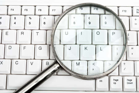 finding: Magnifying glass on an white keyboard