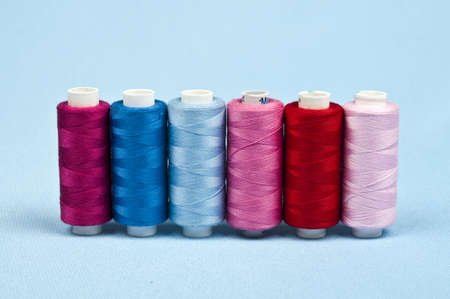 Thread on blue material background photo