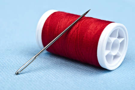 Needle and thread on blue material photo