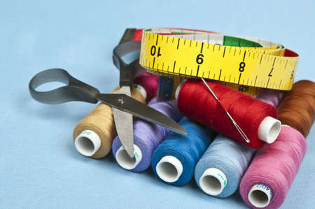 tailor measuring tape:  Tailor tools on blue material background Stock Photo