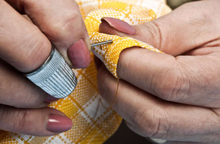 to sew: Woman hands sewing yellow material Stock Photo