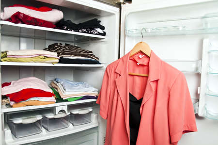 refrigerator with food: Refrigerator close up with clothes inide