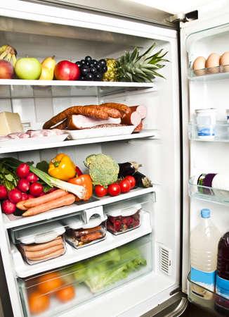 refrigerador: Refrigerador lleno de alimentos cerca de