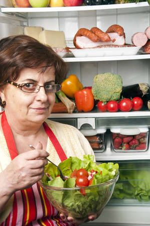 Refrigerator close up with mature woman Stock Photo - 9345772
