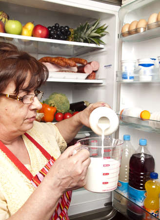 Refrigerator close up with mature woman Stock Photo - 9345782