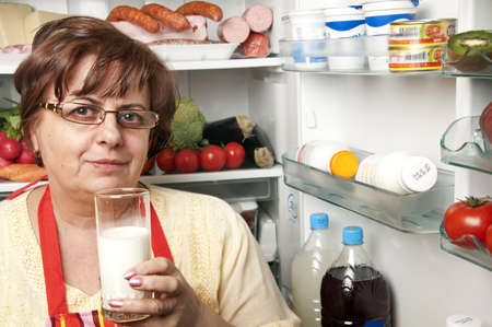 Refrigerator close up with mature woman photo