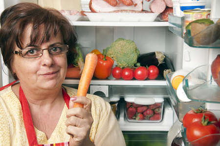 Refrigerator close up with mature woman Stock Photo - 9345763