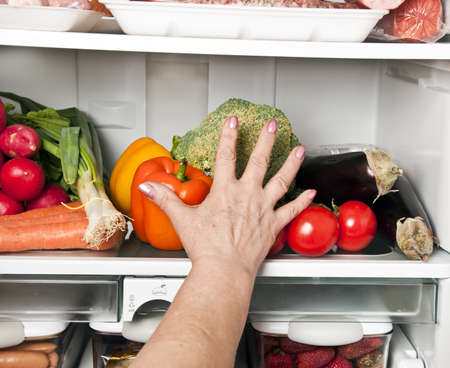 refrigerator with food: Woman hands grab vegetables from refrigerator
