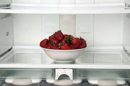 Refrigerator close up with strawberry bowl photo