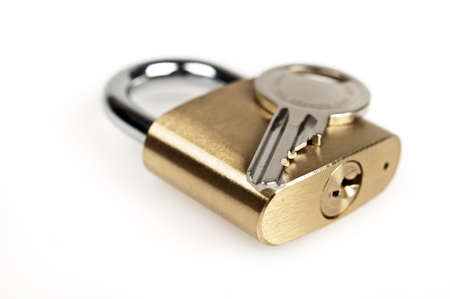golden key: Padlock and key on white