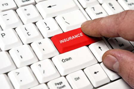 insurance consultant: Insurance key pressed by male hand Stock Photo