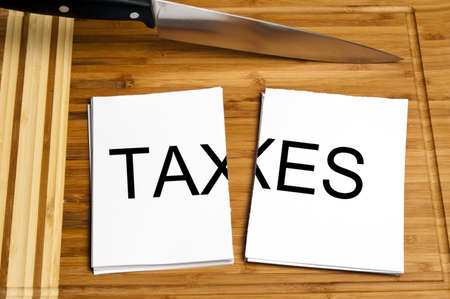blade cut: Knife cut paper with taxes word Stock Photo