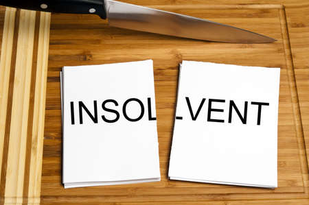 insolvent: Knife cut paper with insolvent word