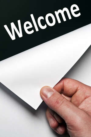 uncovering: Welcome word discovered by male hand Stock Photo