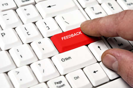 opinions: Feedback key pressed by male hand Stock Photo
