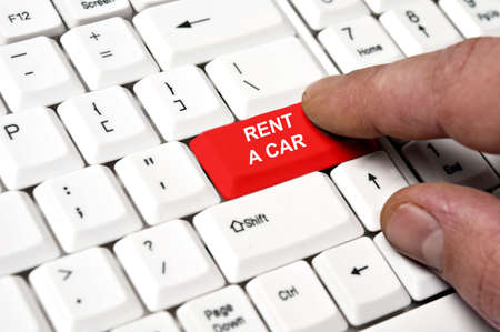 use computer: Rent a car key pressed by male hand