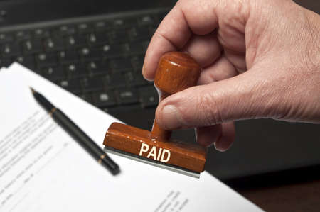 paid stamp: Paid stamp in male hand Stock Photo
