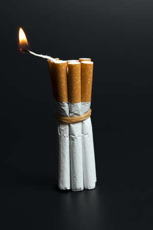 Cigarettes in dynamite concept on black photo