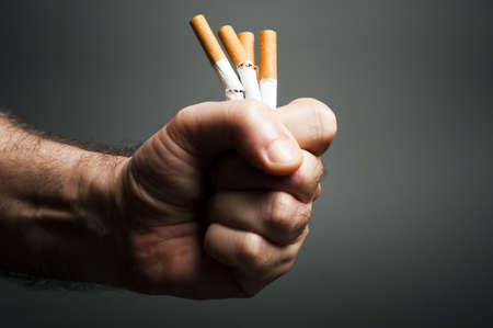 cancerous: Cigarettes in fist on black
