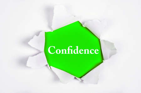 discovered: Confidence word discovered under paper Stock Photo