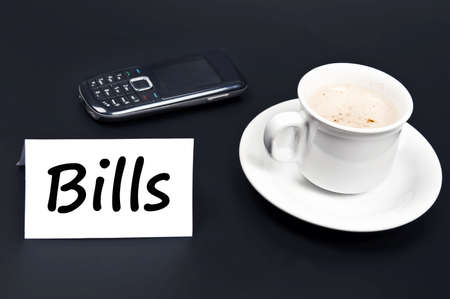 noted: Bills noted on desk with coffee