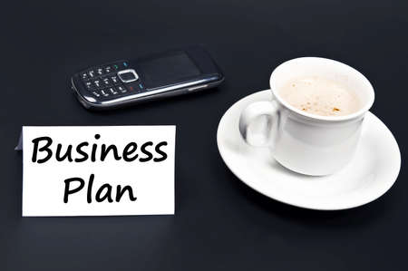 noted: Business plan noted on desk with coffee