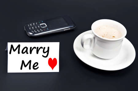 Marry me message on desk with coffee photo