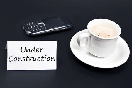 Under construction message on desk with coffee photo