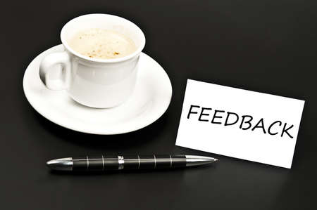 noted: Feedback noted on desk with coffee