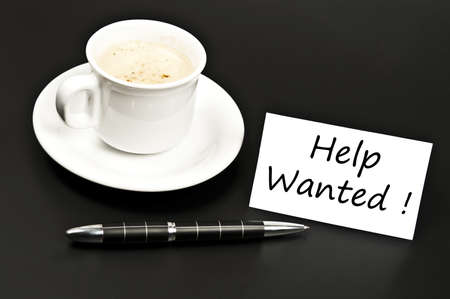 noted: Help wanted  noted on desk with coffee Stock Photo
