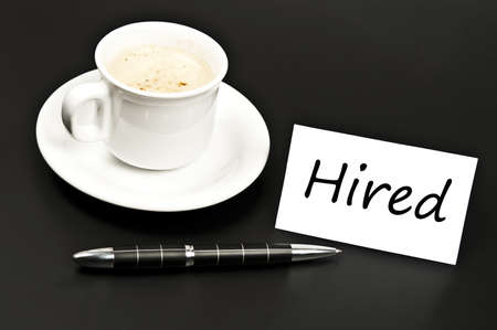 noted: Hired noted on desk with coffee