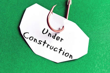 Under Construction message on paper on green background photo