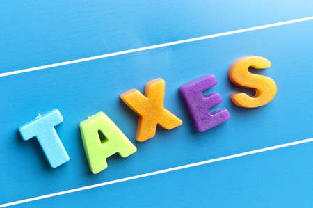 attachement: Taxes word on blue board Stock Photo