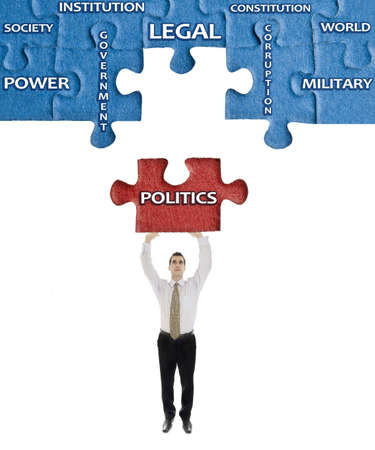 Politics word on puzzle in man hands