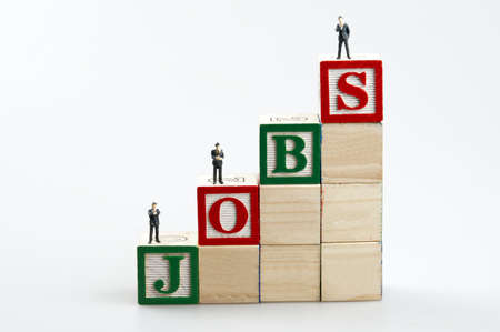 employment elementary school: Jobs word and business man toy Stock Photo