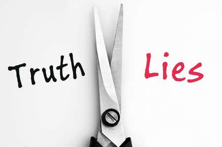 Verdad y mentira las palabras con las tijeras en la media Foto de archivo