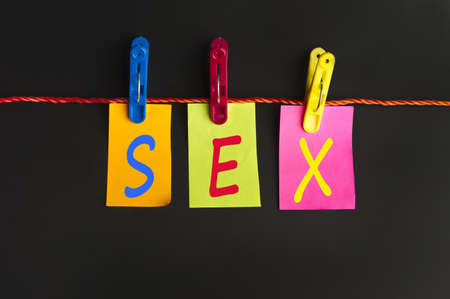 sex education: Sex word on laundry hook on black background