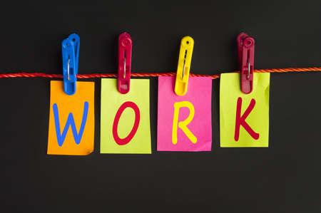 Work word on laundry hook on black background Stock Photo - 11857937