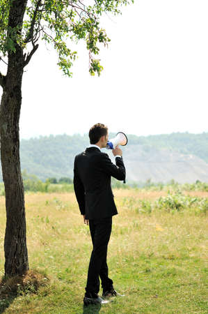 Business man with loudspaker in nature Stock Photo - 14465283