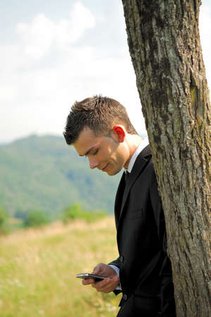Business man with phone in nature photo