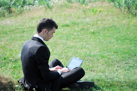 Business man with laptop in nature photo