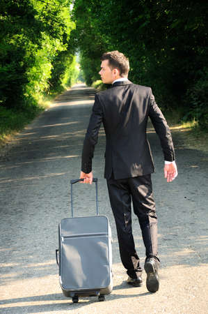 Business man with luggage on road