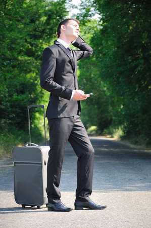 Business man with luggage on road photo