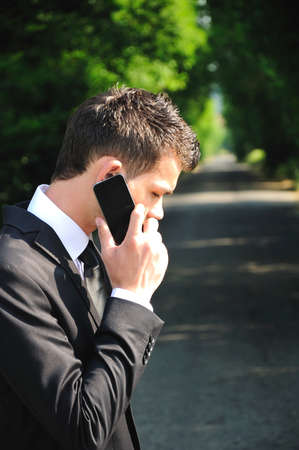 businessman waiting call: Business man with phone on road