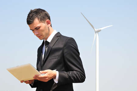 Business man with tablet at wind farm photo