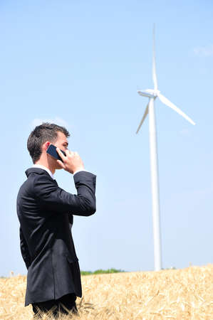 Business man with phone at wind mill photo