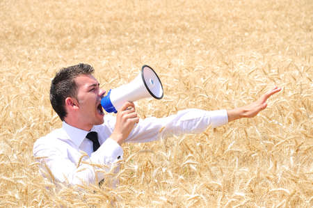 Business man with loudspeaker in wheat photo