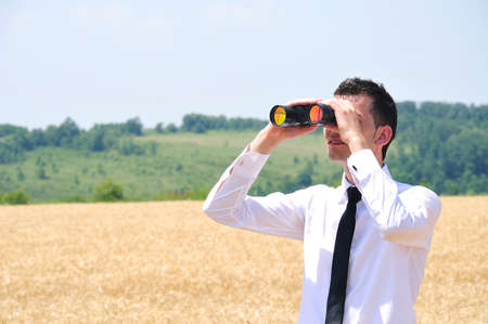 Business man with binocular in wheat photo